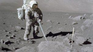 Cientista-astronauta colhendo amostras de rochas lunares.
