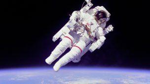 Astronauta no espaço, em missão extra-veicular, com a terra ao funto